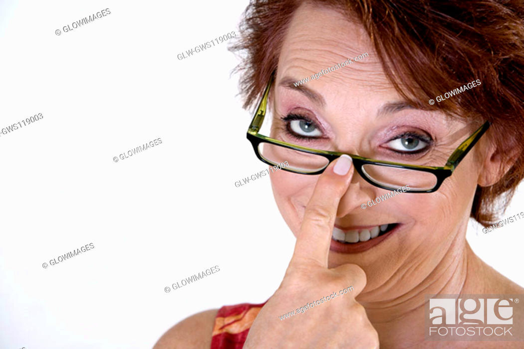 Stock Photo: Portrait of a senior woman adjusting her eyeglasses.