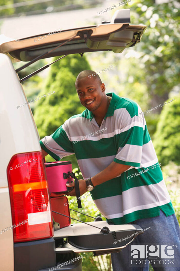 Stock Photo: African man unloading luggage from trunk of SUV.