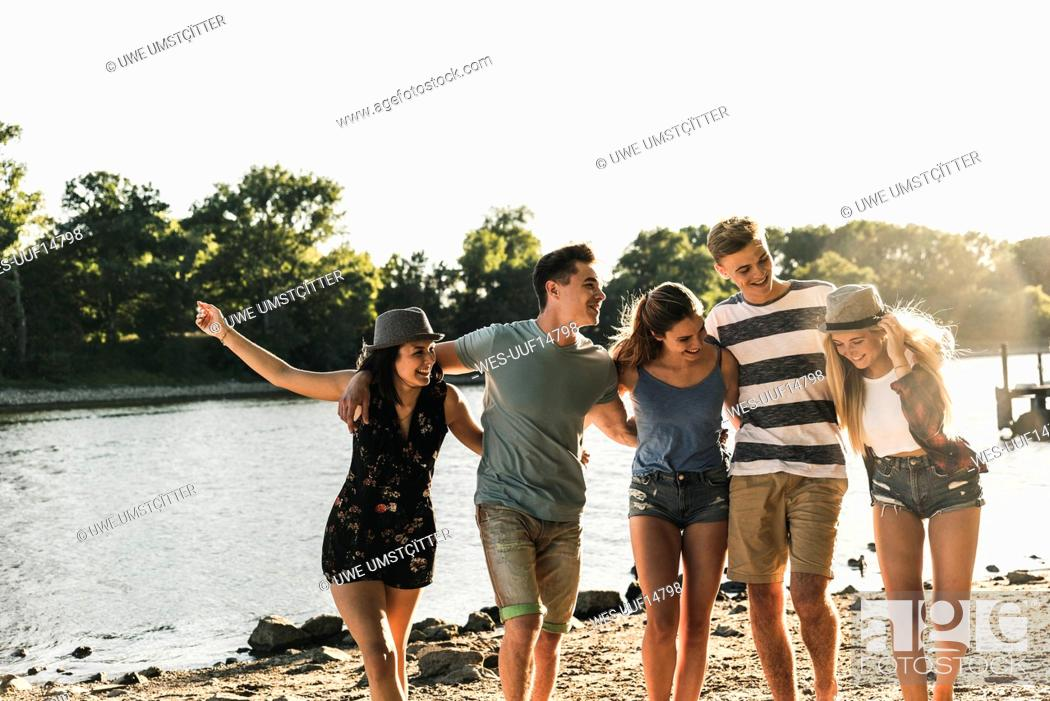 Stock Photo: Group of happy friends arm in arm at the riverside.