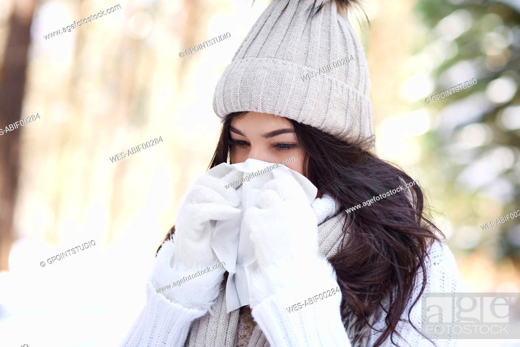 Stock Photo: Young woman blowing nose in winter.