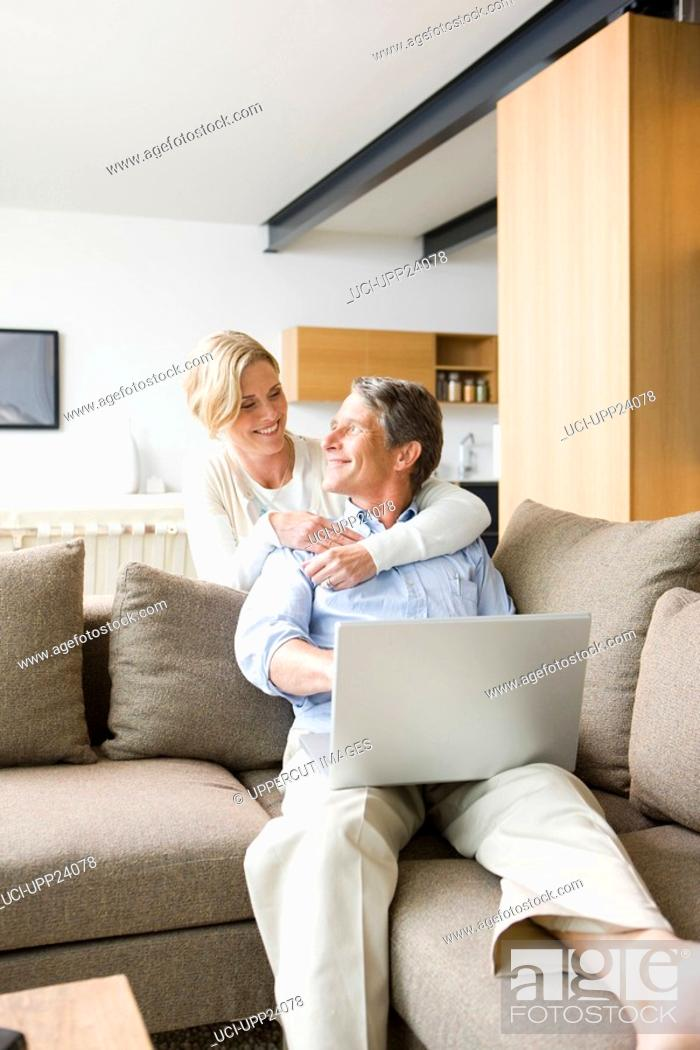 Stock Photo: Woman hugging man using laptop in living room.