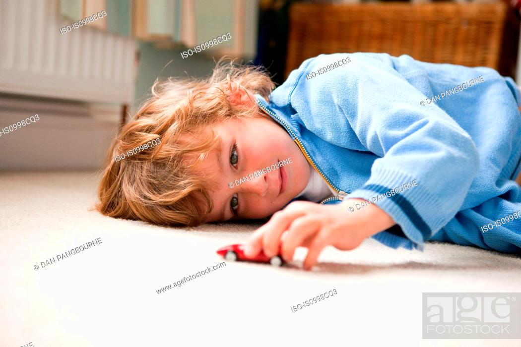 Stock Photo: Young boy lying on his side playing with a toy car.