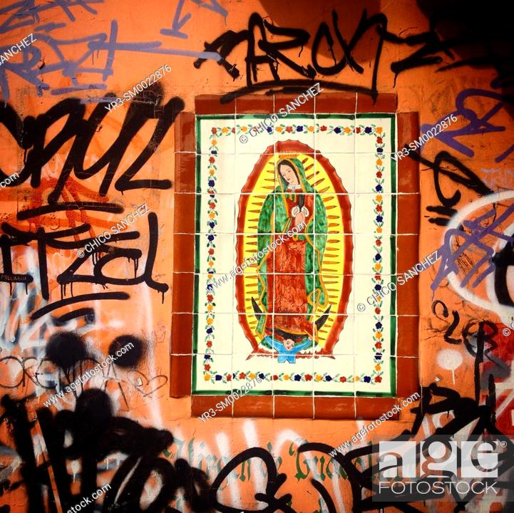 Stock Photo: An image of Our Lady of Guadalupe surrounded by graffiti in Mexico City, Mexico.