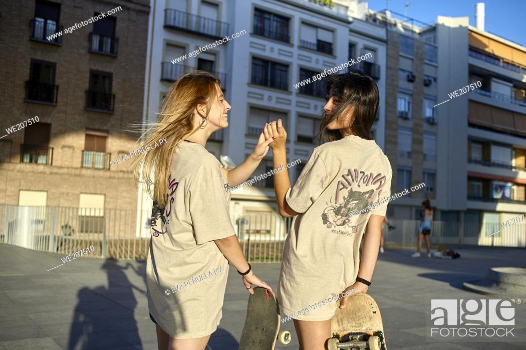 Stock Photo: A couple of young women riding on skateboards in the city.