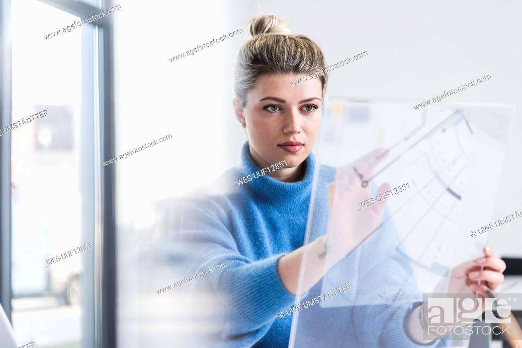 Stock Photo: Young woman working on transparent design in office.