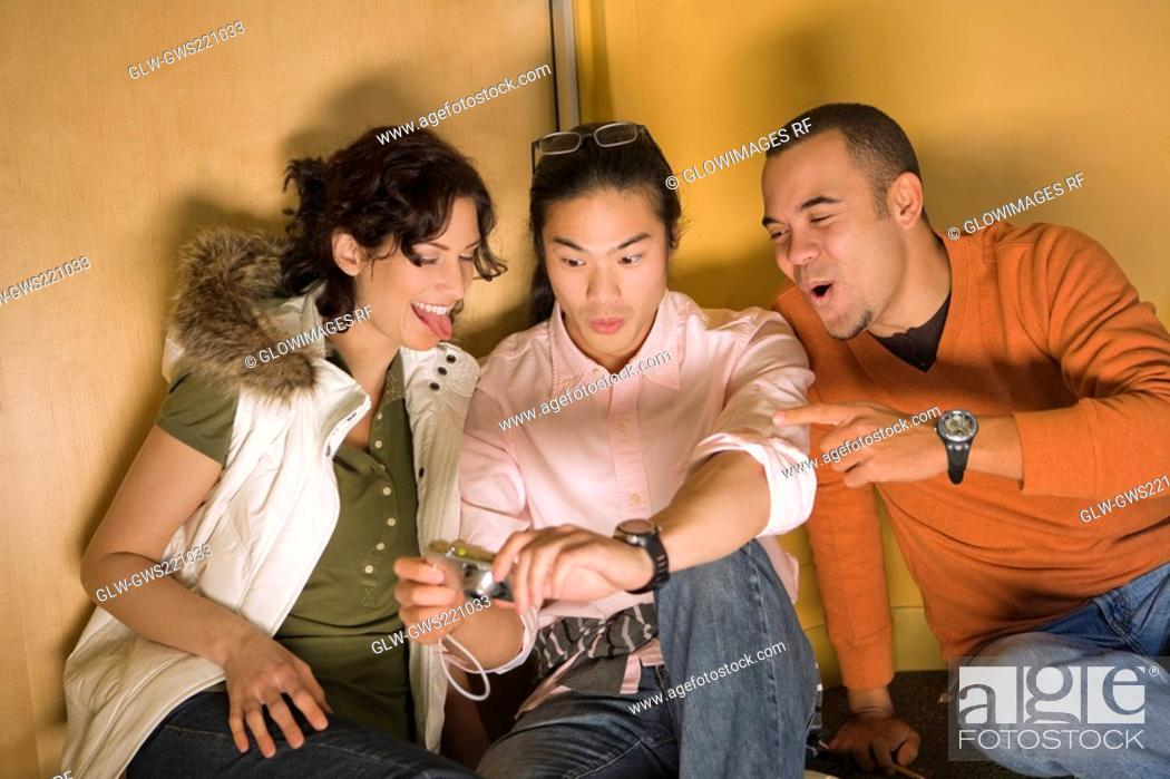 Stock Photo: Two young men with a young woman looking at a digital camera.