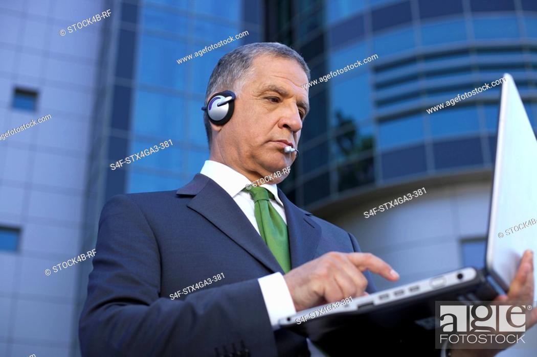 Stock Photo: Mature man with headset using a laptop.