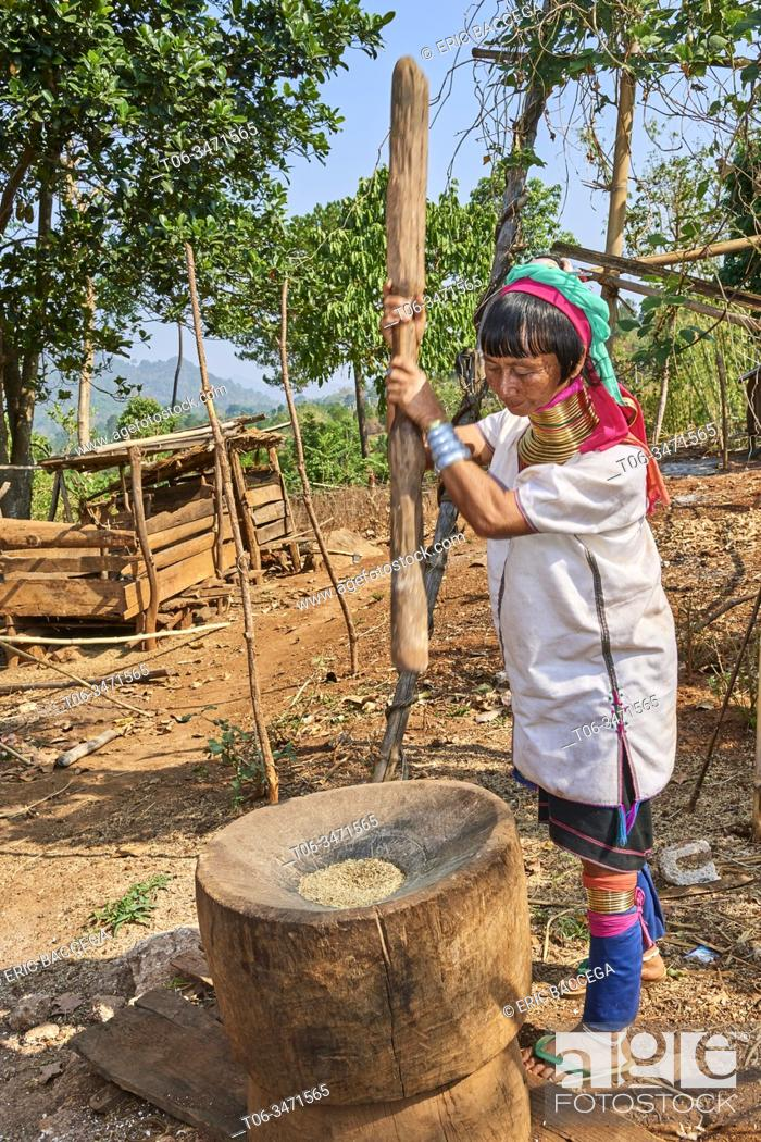 Stock Photo: Kayan Lahwi woman with brass neck coils and traditional clothing pounding rice in a wooden mortar. The Long Neck Kayan (also called Padaung in Burmese) are a.