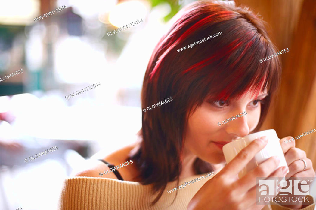 Stock Photo: Close-up of a young woman drinking coffee.