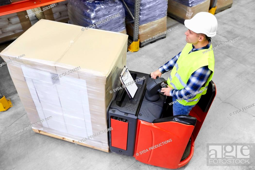 Stock Photo: loader operating forklift at warehouse.