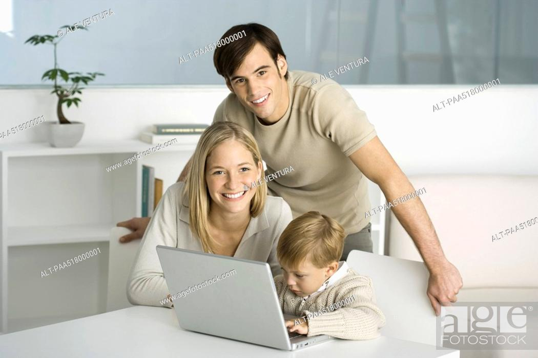 Stock Photo: Family gathered around laptop computer, little boy typing, parents smiling at camera.