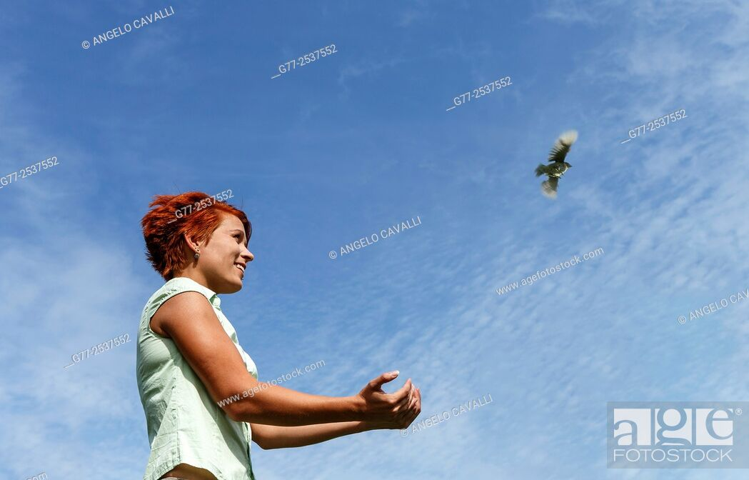 Stock Photo: Woman releasing a bird. Budapest, Hungary.