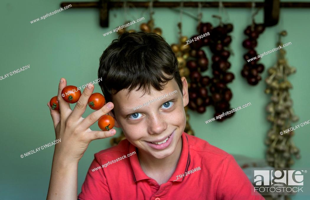 Stock Photo: Russia. Boy cut raw vegetables on the kitchen table.