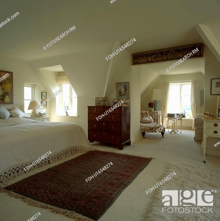 Stock Photo Oriental Rug On Cream Carpet In Large Attic Bedroom