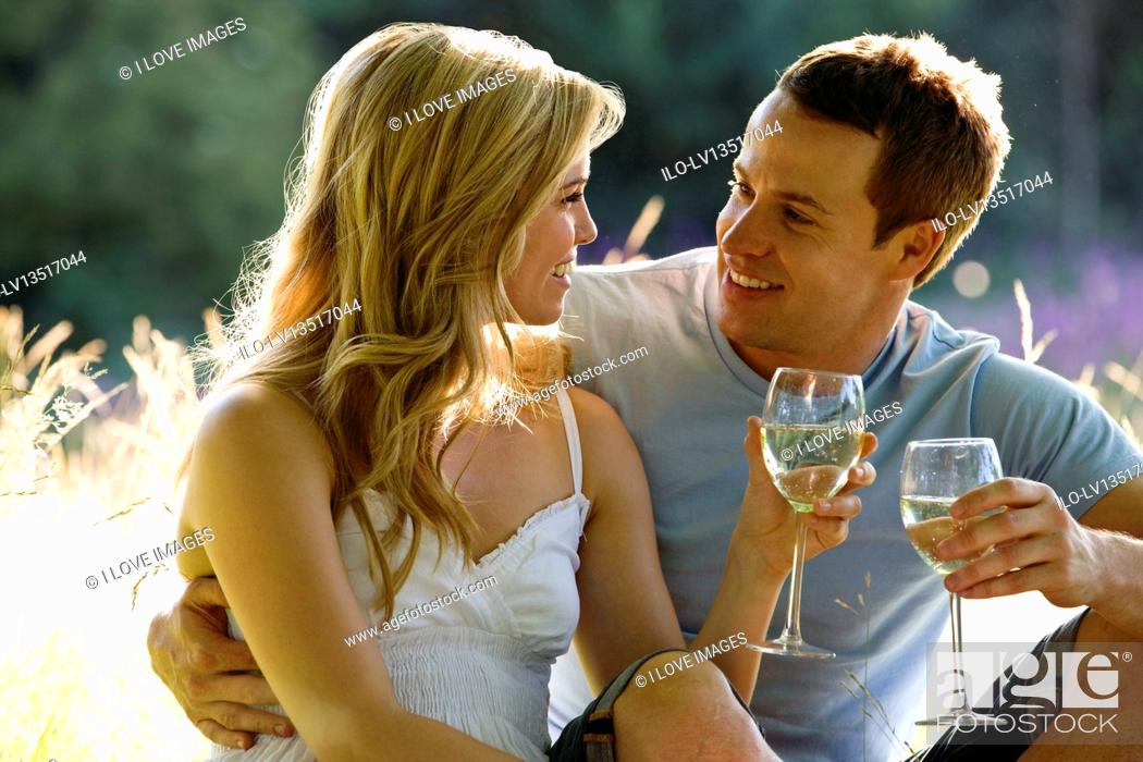 Stock Photo: A young couple sitting on the grass, drinking wine.