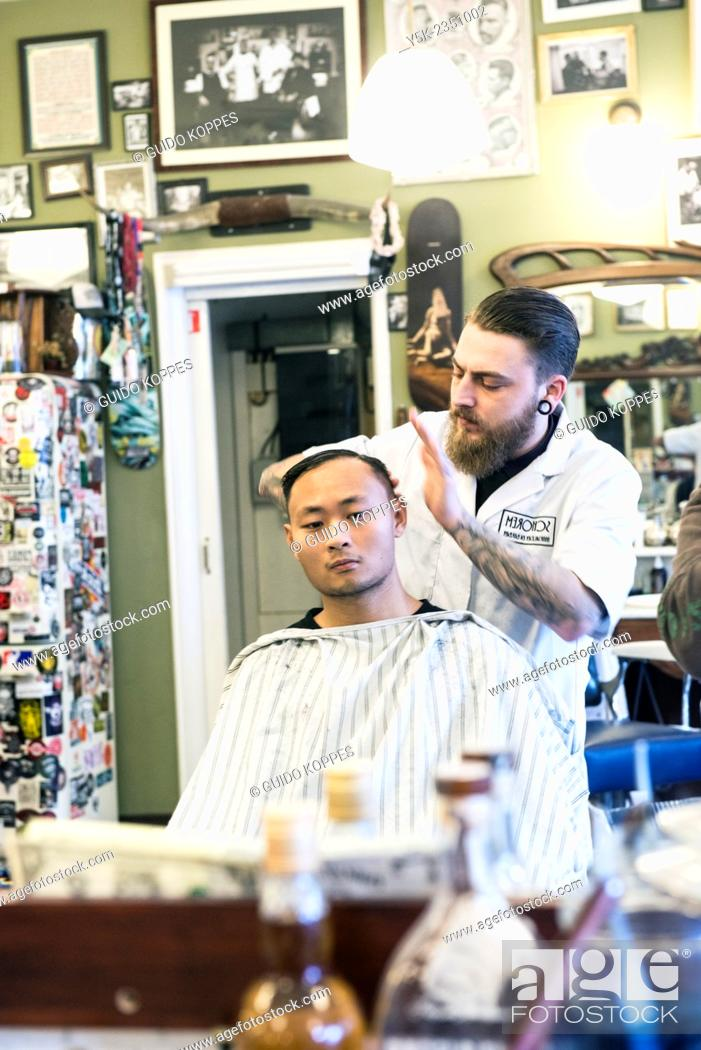 Imagen: Rotterdam, Netherlands. Barber store Schorem. Barber helping his customer in his barber shop by cutting and modeling his hair.