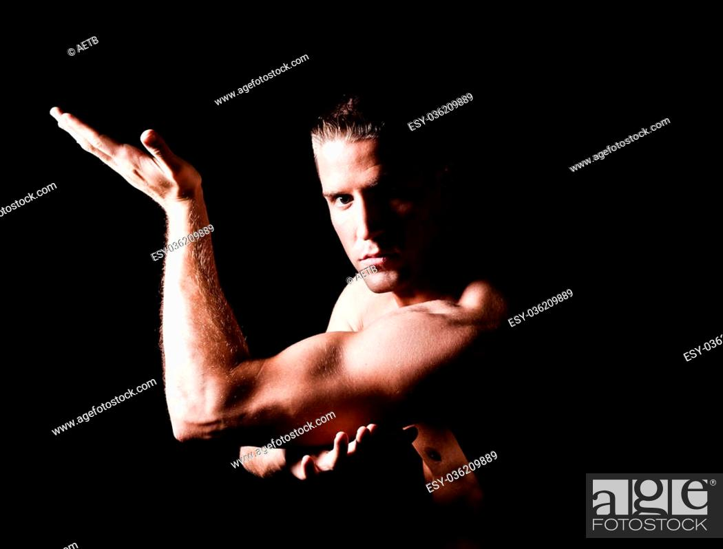Stock Photo: Muscular man isolated on black background.