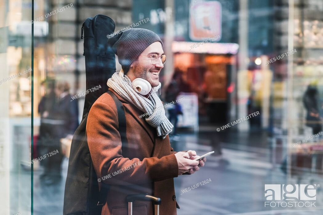 Stock Photo: Smiling young man with guitar case and cell phone.