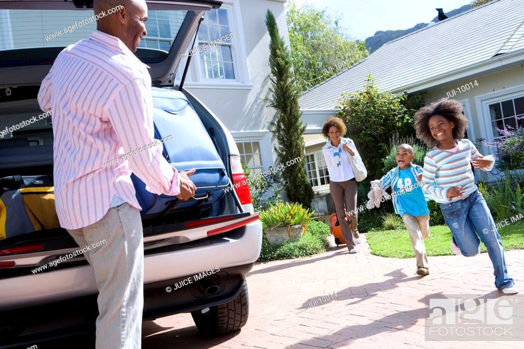 Stock Photo: Man putting suitcase in back of car, smiling at son and daughter 6-10, tilt.