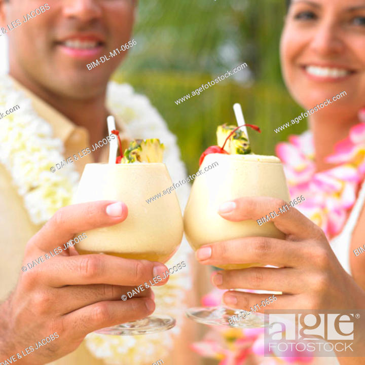 Stock Photo: Couple toasting each other with tropical drinks.