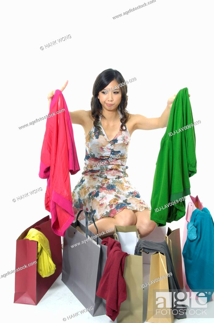 Stock Photo: Woman shocked while looking at clothes near shopping bags.