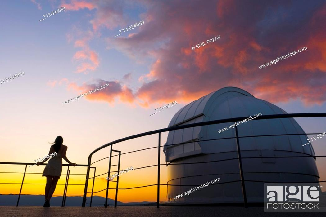 Stock Photo: Young woman is standing next to space observatory telescope dome in sunset.