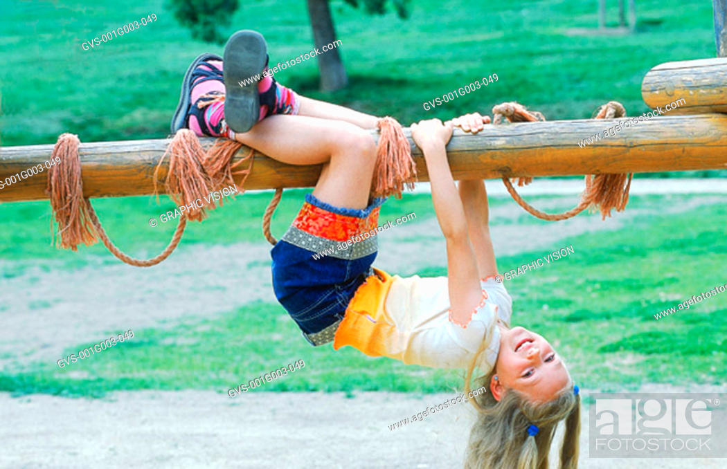 Stock Photo: Young girl hanging from a jungle gym.