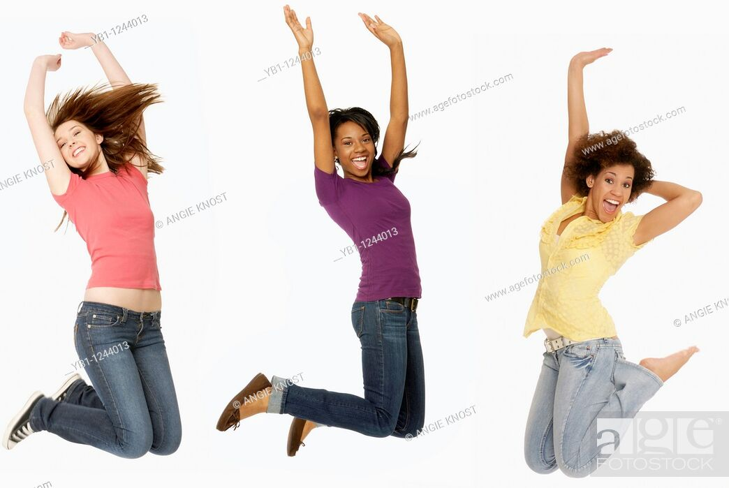 Stock Photo: Three teenage girls jumping in the air with arms up, on solid white background.