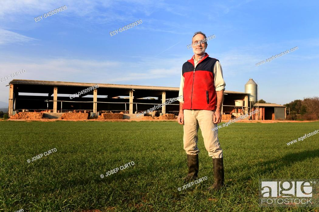 Imagen: Portrait of a farmer in the countryside with a farm at sunset background.
