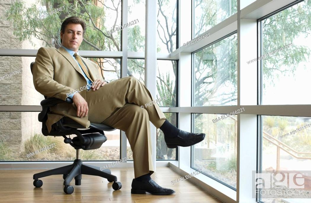 Stock Photo: Confident Hispanic businessman sitting in chair.