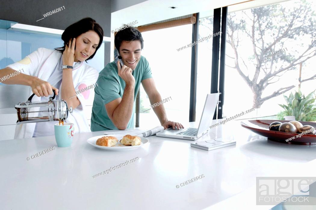 Stock Photo: Young couple talking on mobile phones in the kitchen.