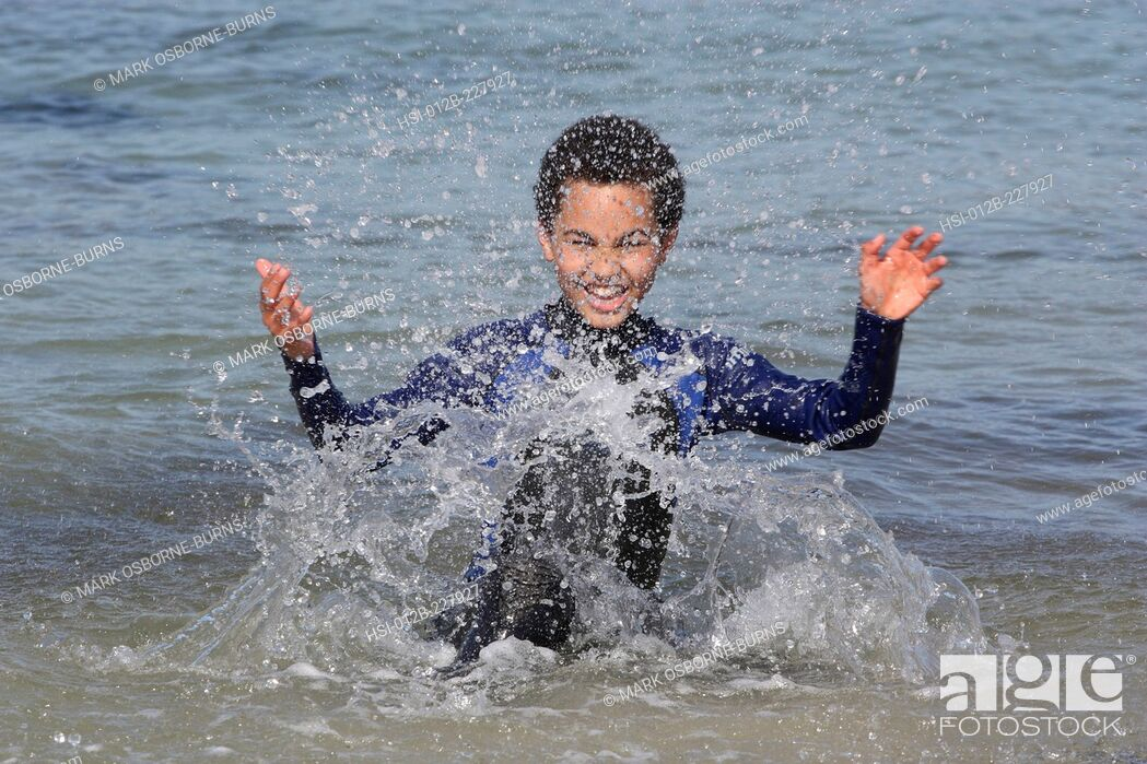 Stock Photo: Young boy 11 years outdoors splashing in the sea.