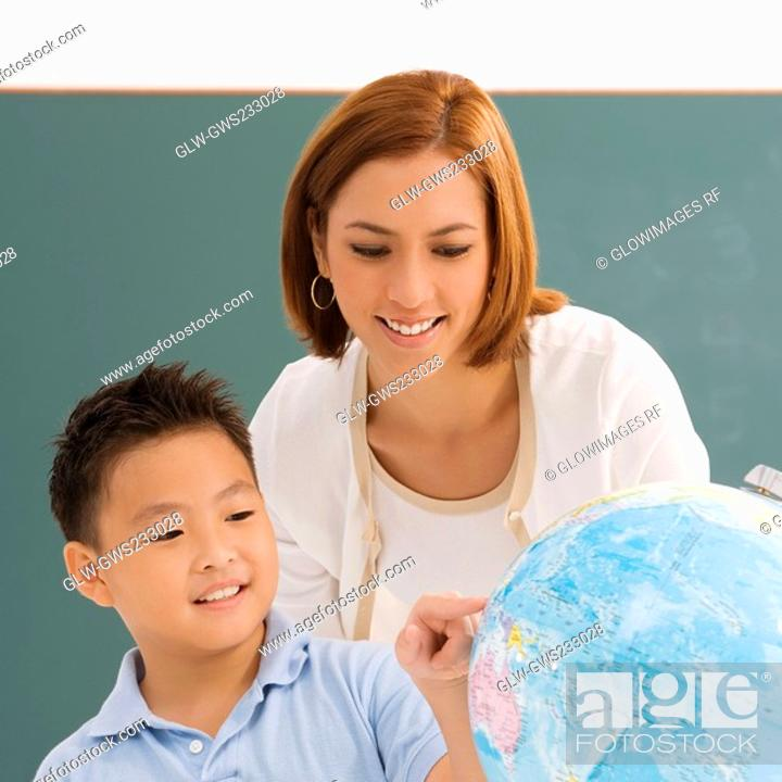 Stock Photo: Close-up of a schoolboy with his teacher looking at a globe and smiling.