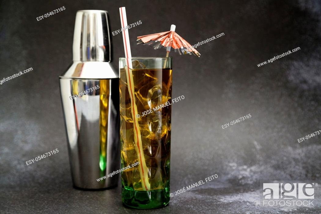 Stock Photo: Iced tea glass with umbrella and straw and cocktail shaker on dark background with copy space.