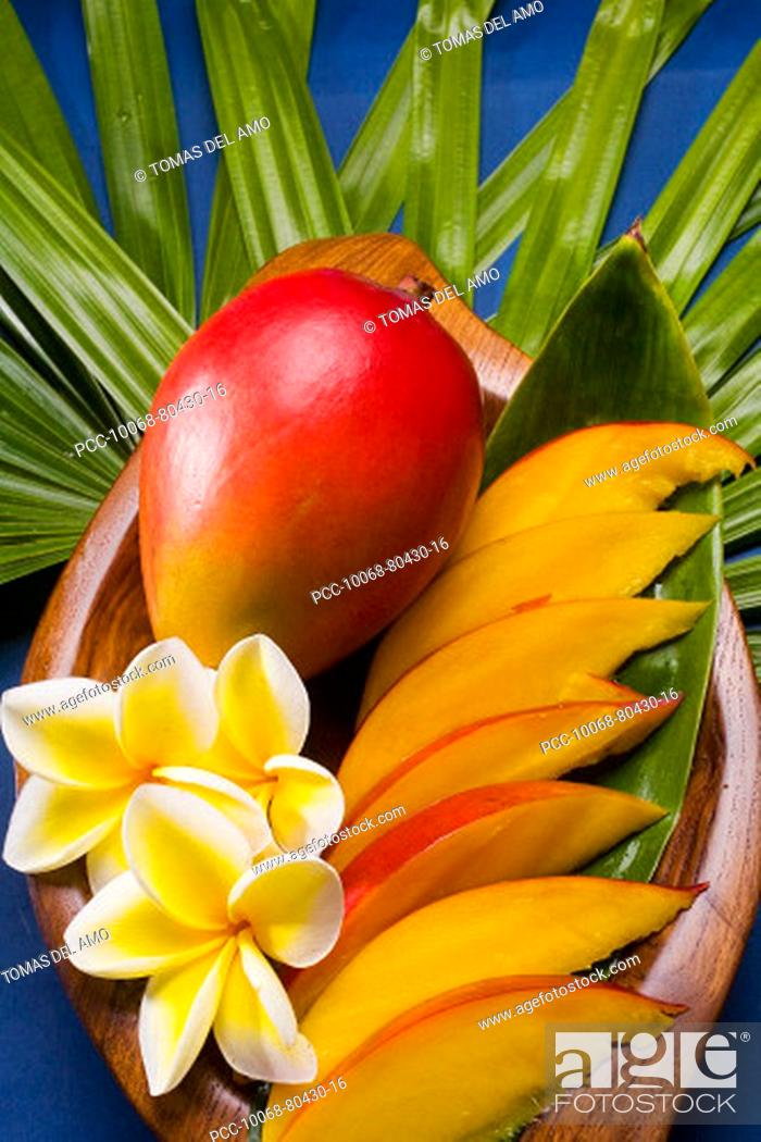 Stock Photo: Studio shot of mango, whole and cut into slices, with flowers.