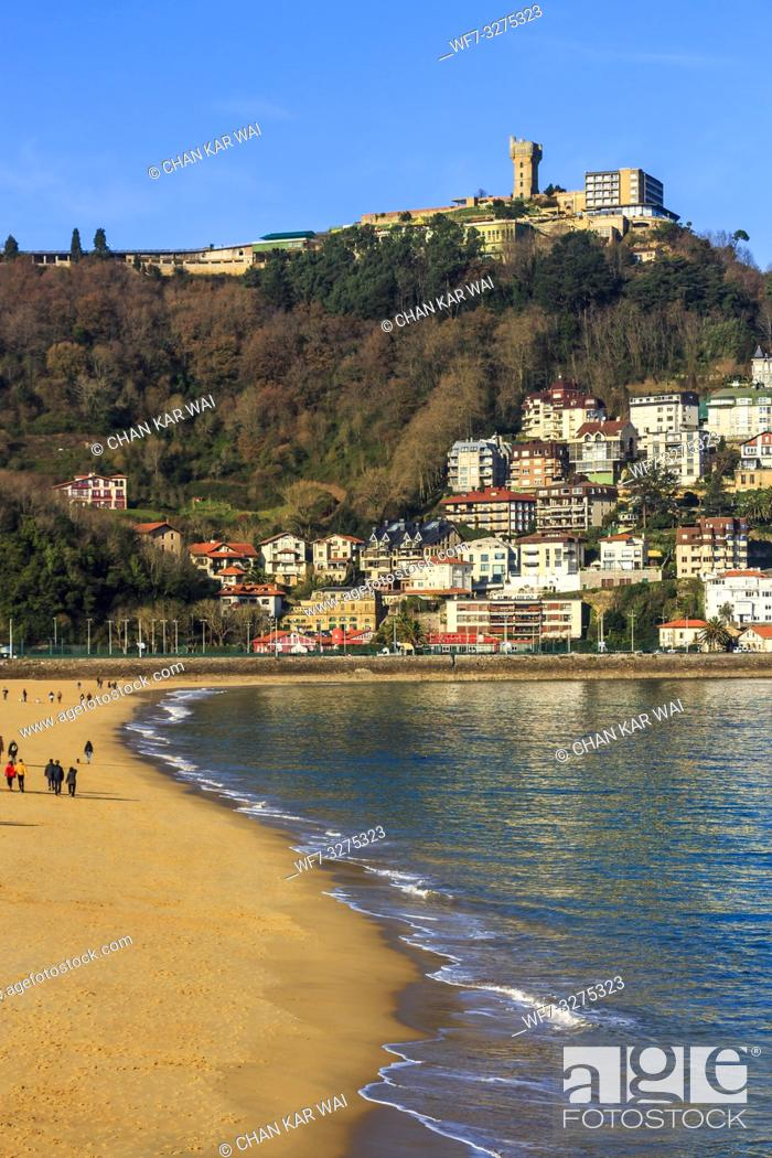 Stock Photo: San Sebastian, Spain - Jan 2019: Ondarreta beach and in the distance houses and apartments on Igeldo mountain range.