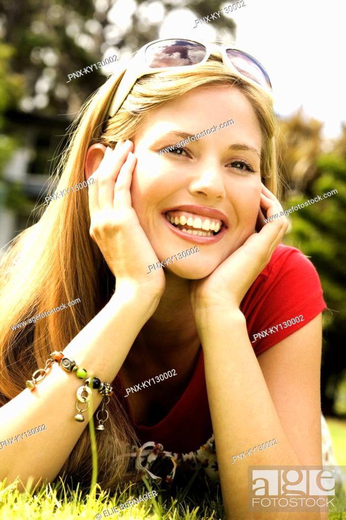 Stock Photo: Young smiling woman lying on grass.