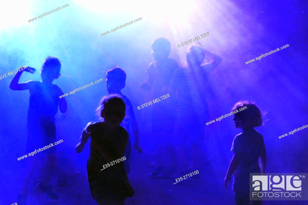 Stock Photo: Children dancing in smoke and blue lights to music played by a disk jockey.