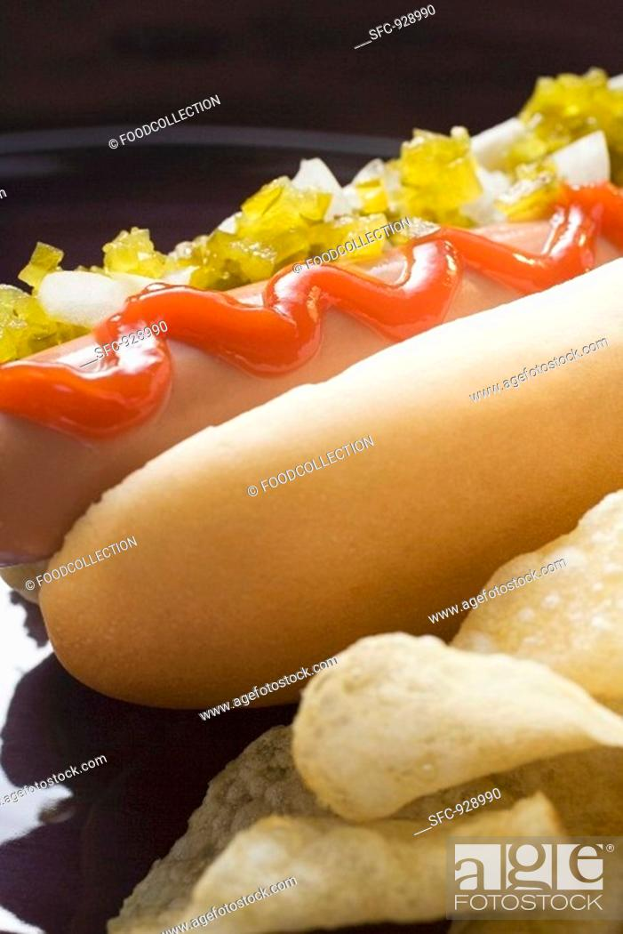 Stock Photo: Hot dog with relish, ketchup, onions and crisps.