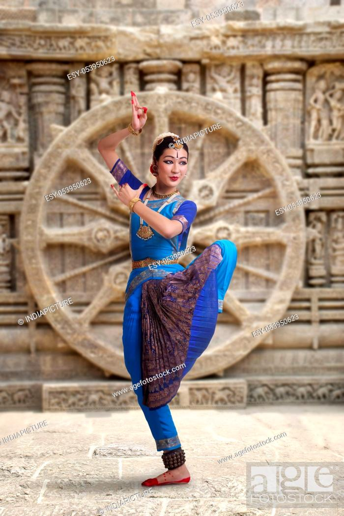 Stock Photo: Full length of Bharatanatyam dancer performing against carved wall.