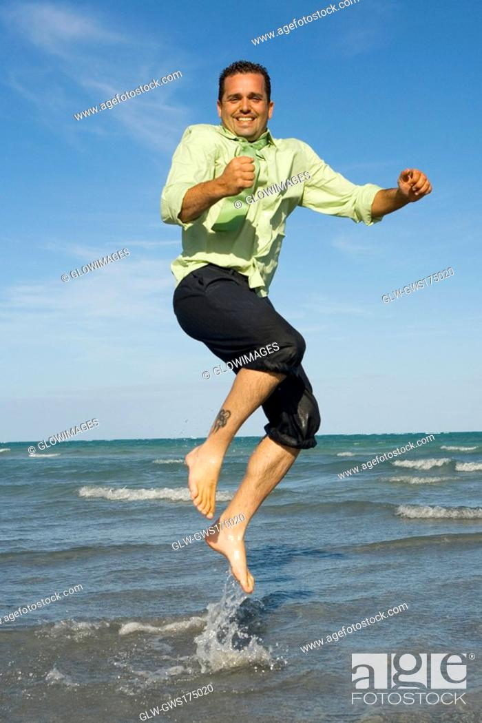 Stock Photo: Mid adult man jumping on the beach.