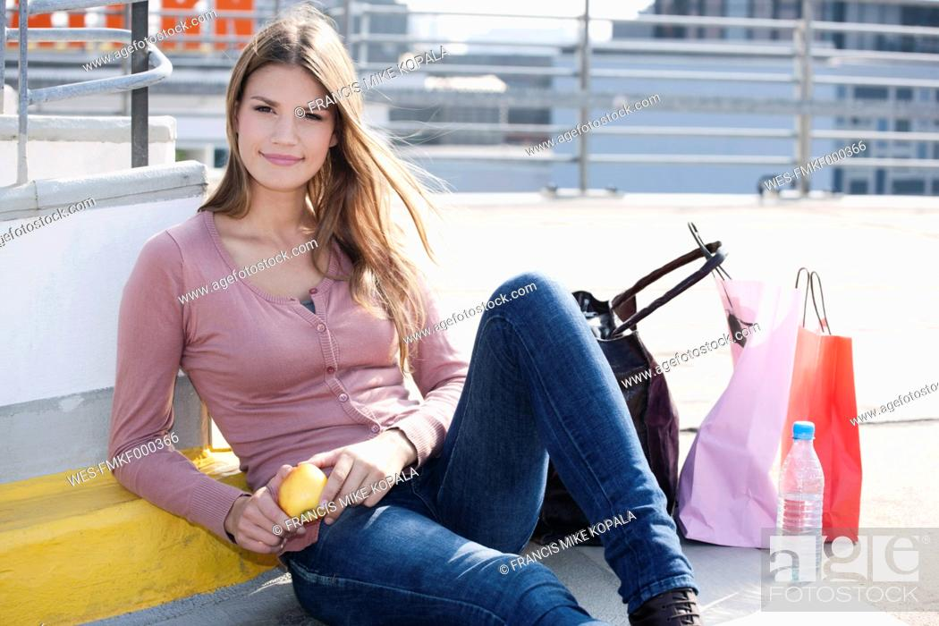 Stock Photo: Germany, Cologne, Young woman with shopping bags, smiling, portrait.