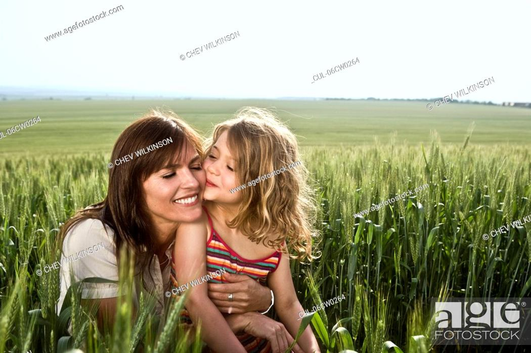 Stock Photo: Child kissing mother in wheat-field.