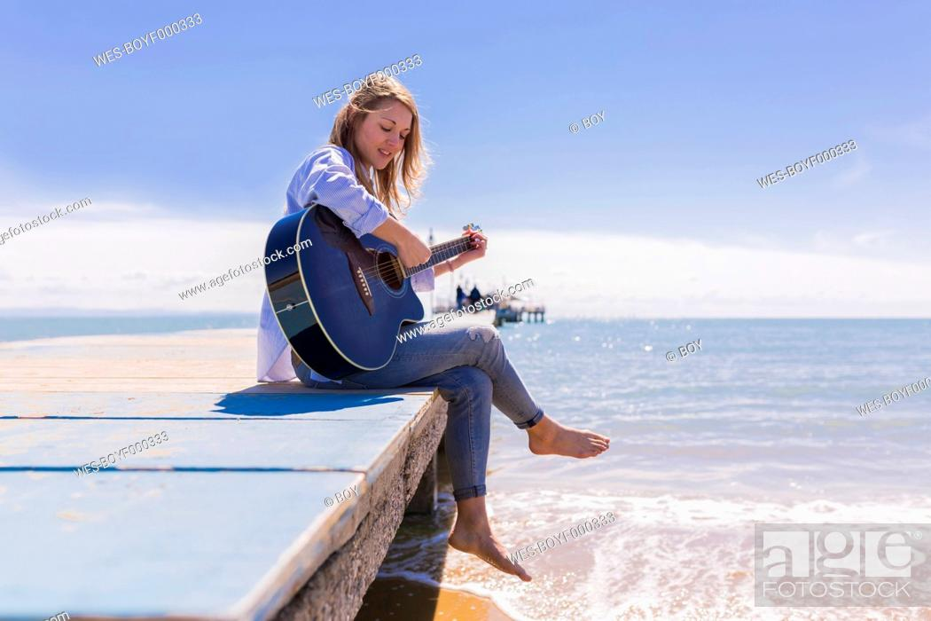 Stock Photo: Young woman with guitar sitting on jetty.