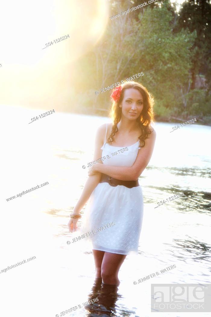 Stock Photo: A beautiful young caucasian woman outdoors in Spokane, Washington, USA, standing in the Spokane River.