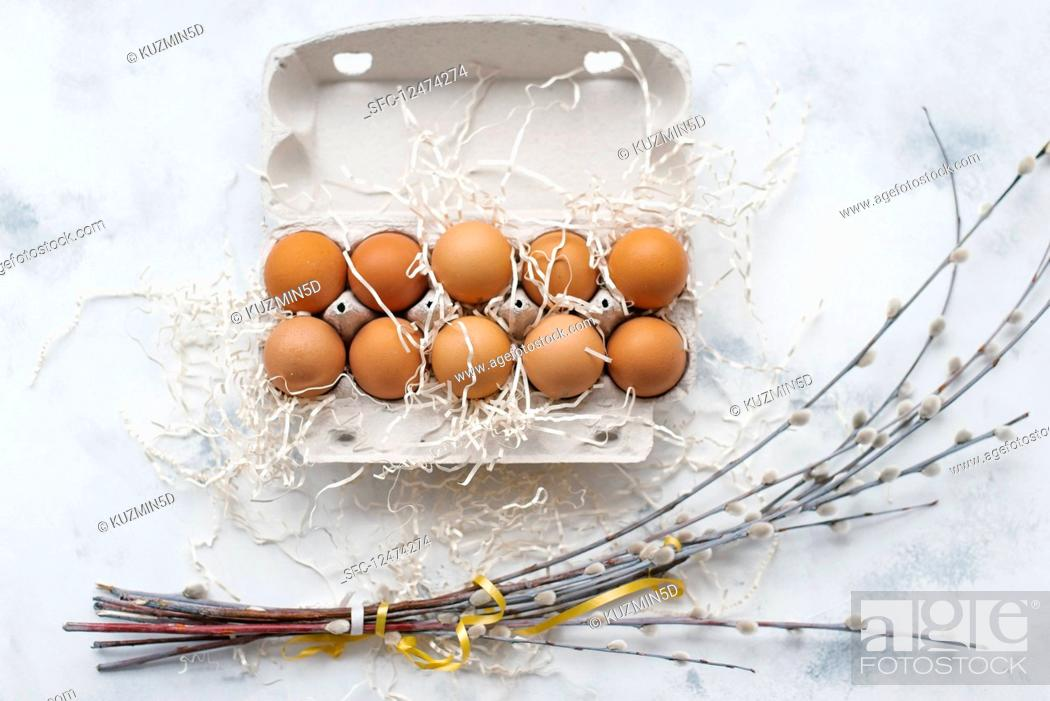 Stock Photo: Eggs in an egg carton and bunches of catkins.
