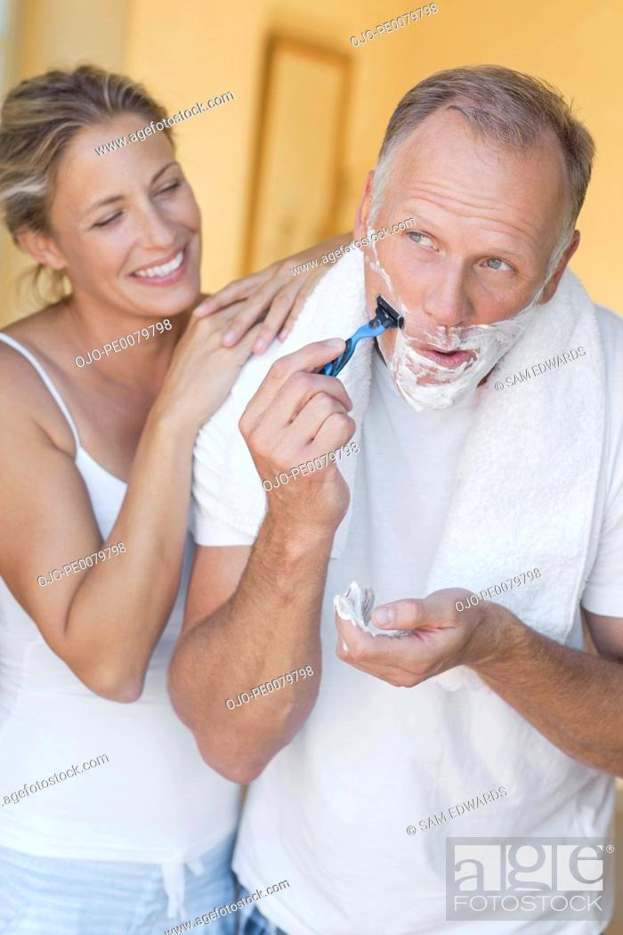 Stock Photo: Woman watching man shave face with razor.