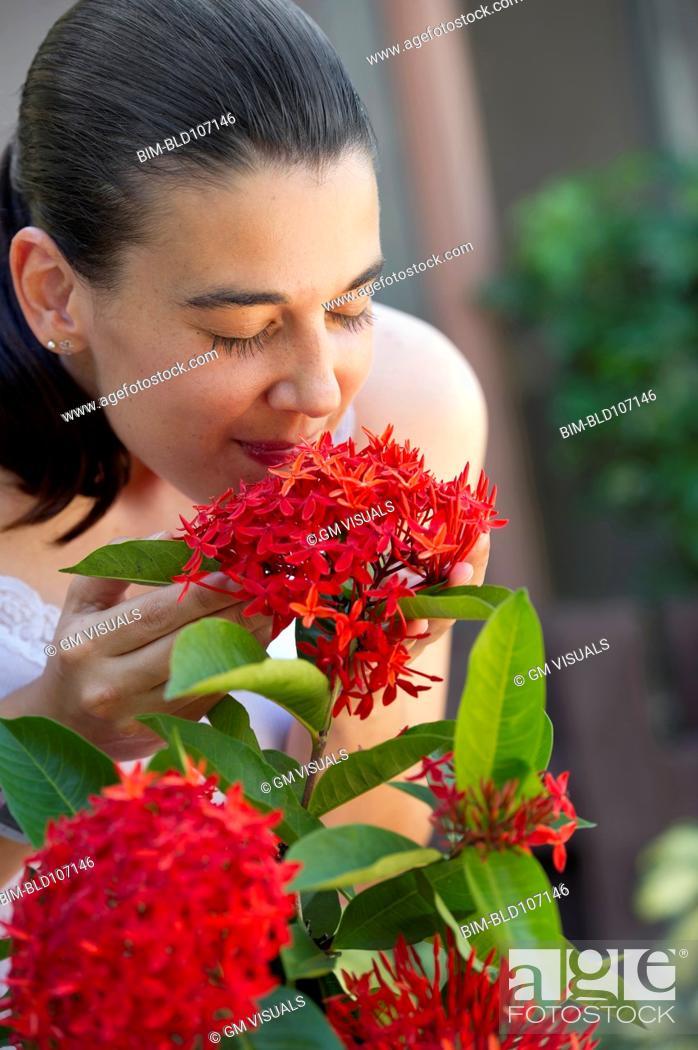 Imagen: Hispanic woman smelling flowers.