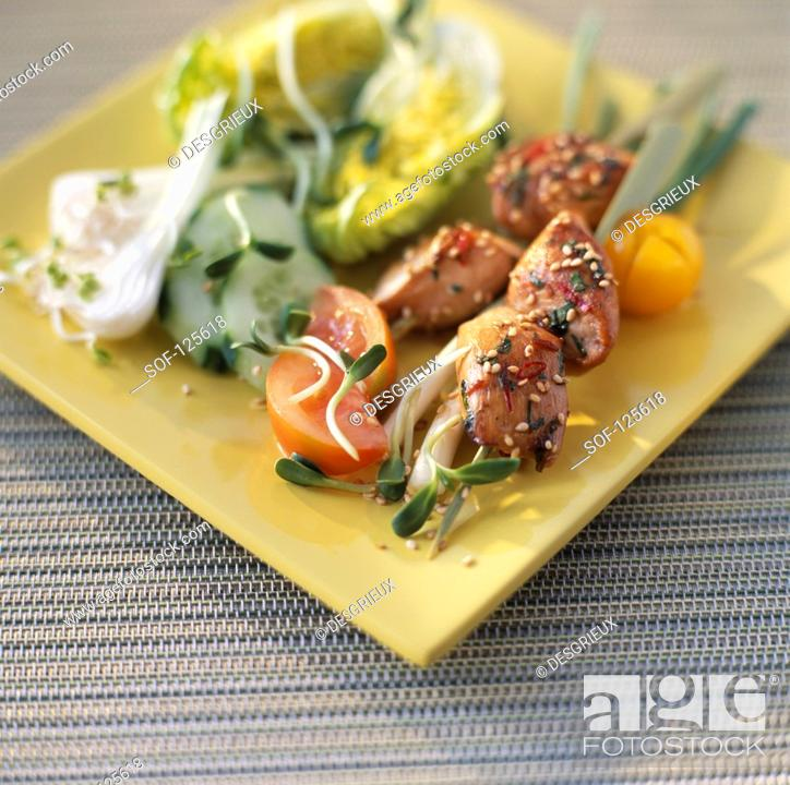 Stock Photo: Chicken kebabs with raw vegetables.