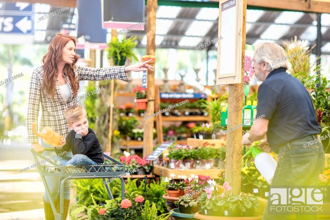 Stock Photo: Gardener helping clients at garden centre.
